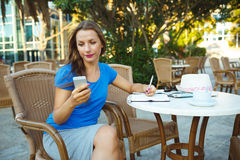 Candid image of a young woman using smartphone and makes notes i Royalty Free Stock Photography