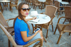Candid image of a young woman using smartphone and makes notes i Royalty Free Stock Image