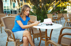 Candid image of a young woman using smartphone and makes notes Stock Image