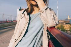 Candid lifestyle cropped close-up photo of young woman. Standing on the bridge smiles and covers her face from sunlight at sunny spring day Stock Photos