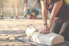 Candid of mature asian female or older runner woman training on CPR demonstrating class in outdoor park and put hands over CPR royalty free stock photos