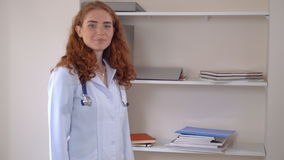 Candid medical worker in clinic. Professional doctor in hospital. Adult woman wearing white lab coat passes by the shelves. Friendly redheaded female with curly stock video