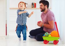 Candid moment of happy father playing with cute baby son at home, family games Royalty Free Stock Photography