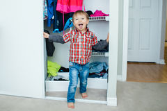 Candid natural portrait of funny cute white Caucasian little boy toddler in wardrobe at home making funny face showing tongue Stock Images