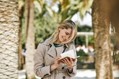 Candid outdoor portrait of cheerful young businesswoman smiling broadly, strolling in the city street at sunny day. Beautiful female searching something in the royalty free stock images