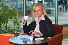 Candid photo of a atractive middle-aged blond businesswoman working. At hotel lobby with a tablet pc and drinking coffe Royalty Free Stock Images