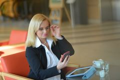Candid photo of a atractive middle-aged blond businesswoman working. At hotel lobby with a tablet pc/smartphone and drinking coffe Stock Images