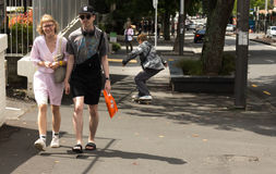 Candid photo senior woman skating. Auckland - February 17, 2017: Candid photography of a couple walking and a senior woman skating in the background Stock Image