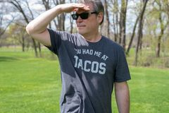 Candid portrait of adult man at the park, shading his eyes with his hand. Candid portrait of man at the park wearing funny t-shirt that says `You had me at tacos stock photography