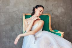 Candid portrait of Ballet dancer ballerina in beautiful light blue dress tutu skirt posing sitting on vinage chair in loft studio. The Candid portrait of Ballet royalty free stock images