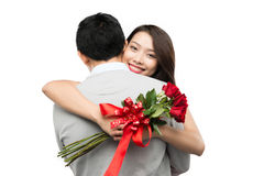 Candid portrait of beautiful Asian couple with rose in love kissing on white background alley celebrating Valentines day - 8 march Royalty Free Stock Photos