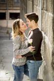 Candid portrait of beautiful European couple with rose in love kissing on street alley celebrating Valentines day. With passion against stone wall on urban Stock Images
