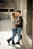 Candid portrait of beautiful European couple with rose in love kissing on street alley celebrating Valentines day. With passion against stone wall on urban Royalty Free Stock Photo