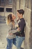 Candid portrait of beautiful European couple with rose in love kissing on street alley celebrating Valentines day Royalty Free Stock Photos