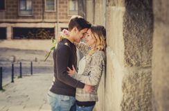 Candid portrait of beautiful European couple with rose in love kissing on street alley celebrating Valentines day. With passion against stone wall on urban Royalty Free Stock Photos