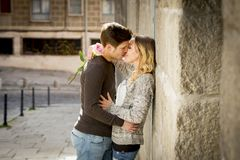 Candid portrait of beautiful European couple with rose in love kissing on street alley celebrating Valentines day. With passion against stone wall on urban Stock Photos