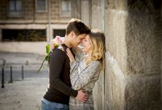 Candid portrait of beautiful European couple with rose in love kissing on street alley celebrating Valentines day. Candid and romantic portrait of beautiful Stock Image