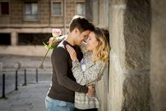 Candid portrait of beautiful European couple with rose in love kissing on street alley celebrating Valentines day Royalty Free Stock Images