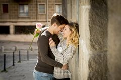 Candid portrait of beautiful European couple with rose in love kissing on street alley celebrating Valentines day Stock Photos
