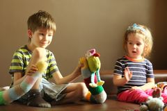 Candid portrait of children playing at home with knitted toys. Emotional facial expressions Royalty Free Stock Images