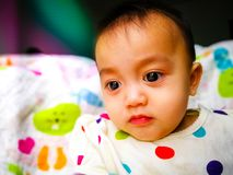 Candid portrait of a cute and expressive Asian baby girl. Lifestyle and childhood concept. stock photography