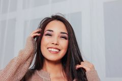 Candid portrait of sensual smiling asian girl young woman with dark long hair in cozy beige sweater, close up. The Candid portrait of sensual smiling asian girl stock photos