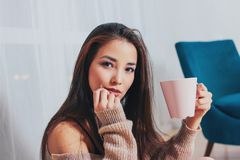 Candid portrait of sensual smiling asian girl young woman with dark long hair in cozy beige sweater holding cup of tea on white. The Candid portrait of sensual stock photo