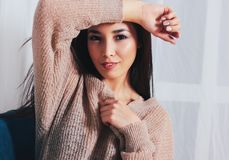 Candid portrait of sensual smiling asian girl young woman with dark long hair in cozy beige sweater sitting on blue vintage chair. The Candid portrait of sensual royalty free stock photography