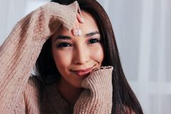 Candid portrait of sensual smiling asian girl young woman with dark long hair in cozy beige sweater sitting on blue vintage chair. The Candid portrait of sensual royalty free stock image