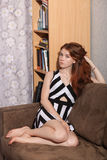 Candid portrait of thoughtful young beautiful redhead woman sitting on sofa touching her gorgeous hair typical room background Royalty Free Stock Photos