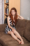 Candid portrait of thoughtful young beautiful redhead woman sitting on sofa typical room background Royalty Free Stock Photos