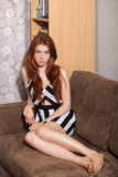 Candid portrait of thoughtful young beautiful redhead woman sitting on sofa typical room background Royalty Free Stock Photography