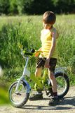 Candid portrait of an upset boy with a bicycle in the sunlit field. Candid portrait of an upset boy with a bicycle in the sunlit summer field stock image