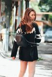 Candid portrait of young beautiful long hair girl fashion model hipster in black hoodie on city street. Candid portrait of young beautiful long hair girl fashion stock photo