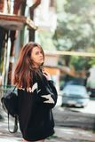 Candid portrait of young beautiful long hair girl fashion model hipster in black hoodie on city street. Candid portrait of young beautiful long hair girl fashion royalty free stock image