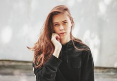 Candid portrait of young beautiful long hair girl fashion model hipster in black hoodie on wall background. Candid portrait of young beautiful long hair girl royalty free stock photo