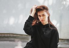Candid portrait of young beautiful long hair girl fashion model hipster in black hoodie on wall background. Candid portrait of young beautiful long hair girl royalty free stock images