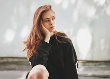Candid portrait of young beautiful long hair girl fashion model hipster in black hoodie on wall background. Candid portrait of young beautiful long hair girl stock photography