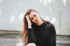 Candid portrait of young beautiful long hair girl fashion model hipster in black hoodie on wall background. Candid portrait of young beautiful long hair girl royalty free stock image