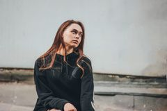 Candid portrait of young beautiful long hair unhappy girl fashion model hipster in black hoodie on dirty wall. Candid portrait of young beautiful long hair stock photography