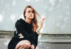 Candid portrait of young beautiful long hair unhappy girl fashion model hipster in black hoodie on wall background. Candid portrait of young beautiful long hair royalty free stock photography