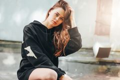 Candid portrait of young beautiful long hair unhappy girl fashion model hipster in black hoodie on wall background. Candid portrait of young beautiful long hair royalty free stock photos