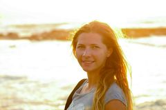 Candid portrait of young woman by the sea at sunset, strong sun backlight, background overexposed intentionally for atmosphere.  stock images