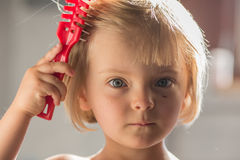 Candid serious thinking or sad young baby caucasian blonde girl with small scratch comb with hair brush at home Stock Images