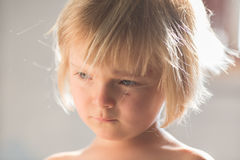 Candid serious thinking or sad young baby caucasian blonde girl with small scratch portrait at home Royalty Free Stock Images