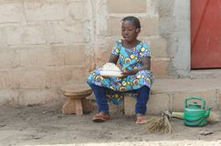 Candid Shot of African Black Girl Cooking Rice Outdoors. Candid shot of black African children outdoors in Bamako, Mali. By buying this image you support our Stock Photo