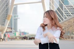 Candid shot of attractive young Asian business woman thinking and dreaming about something at city background. Candid shot of attractive young Asian business Stock Photo