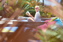 Candid shot of lady reading book and relaxing in lush tropical garden. Fancy lady in white beach tunic reading book and relaxing by poolside of luxury spa stock photos