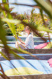 Candid shot of lady reading book and relaxing in lush tropical garden. Fancy lady in white beach tunic reading book and relaxing by poolside of luxury spa stock image