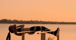 Candid shot of real healthy and fit woman performing hanging leg raises on outdoor fitness station in sunset at beach. Promenade. Showing strong abdominal six stock video footage